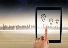 Holding tablet and city with marker location pointers. Digital composite of Holding tablet and city with marker location pointers Stock Photography