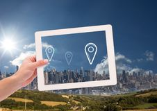 Holding tablet and City with marker location pointers. Digital composite of Holding tablet and City with marker location pointers Royalty Free Stock Photo