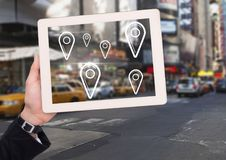 Holding tablet and City with marker location pointers. Digital composite of Holding tablet and City with marker location pointers Stock Photos