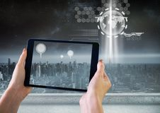 Holding tablet and City with marker location pointers and interface technology. Digital composite of Holding tablet and City with marker location pointers and Royalty Free Stock Image