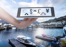 Holding tablet and currency upload online over marina. Digital composite of Holding tablet and currency upload online over marina Stock Photography