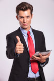 Holding tablet & making thumbs up gesture Royalty Free Stock Photo