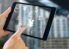 Holding tablet and Mixed Currency icons over city Royalty Free Stock Photos