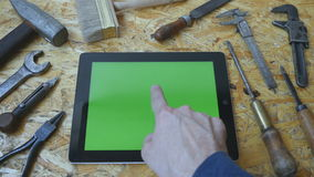 Holding tablet pc in landscape mode with workshop table with carpentry tools in the background. Man hand using tablet stock footage