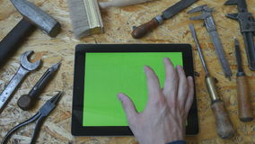 Holding tablet pc in landscape mode with workshop table with carpentry tools in the background. Man hand using tablet stock video