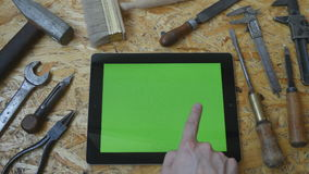 Holding tablet pc in landscape mode with workshop table with carpentry tools in the background. Man hand using tablet stock video footage