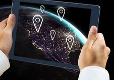 Holding tablet and Planet earth with marker location pointers. Digital composite of Holding tablet and Planet earth with marker location pointers Stock Photography
