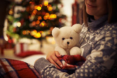 Holding teddybear. Young woman with teddy bear enjoying Christmas eve at home Royalty Free Stock Photo