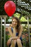 Holding teenager un aerostato rosso Fotografia Stock Libera da Diritti