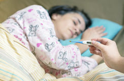 Holding thermometer over a sick woman Stock Photo
