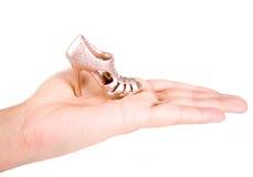 Holding the tiny golden shoe. Female holding the tiny glitter gold shoes stock image