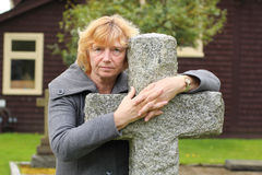 Holding on to stone cross. A mature woman with her arms around a stone/cement cross in a church graveyard Royalty Free Stock Photography