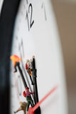 Holding On To Time. Macro of miniature model mountaineers scaling the hands of a clock, shallow DOF Stock Photos