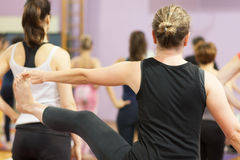 Holding toes during yoga class Stock Photo