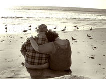 Holding Together. An older couple close together on the beach. Part of my sepia toned retired couple on the beach series. Keyword sereis1rc to see the entire Stock Photos
