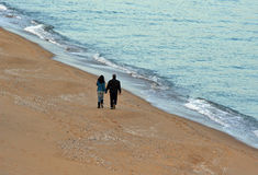 Holding together. Man and woman holding together and walking at sea stock images