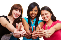 Holding together thumbs up. Three young happy woman showing their thumbs up Stock Image