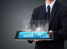 Holding touch screen tablet with a graph Stock Images