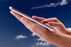 Holding touch screen tablet. On the sky background Stock Photos