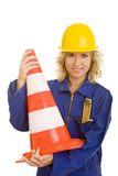 Holding a traffic cone. Young woman with helmet and a jumpsuit holding a traffic cone royalty free stock images