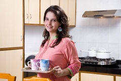 Holding tray with mugs. Young woman holding tray with mugs in kitchen Royalty Free Stock Photography