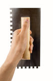 Holding the trowel. Craftsperson holding the trowel over white wall royalty free stock image