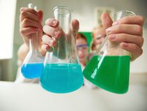 Holding tubes. Three tubes with chemical liquids held by schoolchildren Stock Photos