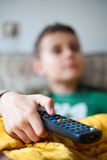 Holding tv remote control Stock Photo