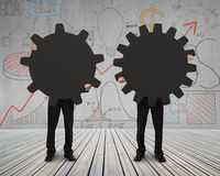 Holding two gears to connect on wooden floor. With doodles Royalty Free Stock Image