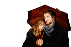 Holding umbrella. A couple standing/holding each other under an umbrella. They are both wearing coats and scarfs, the men holds the umbrella. Isolated on white Royalty Free Stock Photo