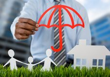 Holding umbrella over insurance cut outs home family with buildings Royalty Free Stock Images
