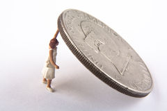 Holding up the dollar. Miniature woman holding up a silver dollar coin Royalty Free Stock Images