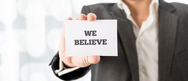 Holding up a white card with We believe sign Stock Photo