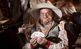 Holding Up Winning Poker Player. Gambler with cards and players guns pointed at him Stock Photography
