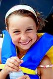Holding-Wasserflasche des jungen Mädchens tragende lifevest. Stockfoto