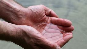 Holding water in cupped hands stock footage