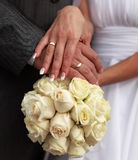 Holding a wedding bouquet. Picture a pair of newlyweds holding a wedding bouquet Stock Photos