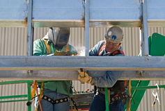 Holding the Weld in Place. Worker holds the metal in place while the other welds it Stock Images