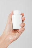Holding a white bottle of pills Royalty Free Stock Image