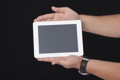 Holding a white digital tablet with bots hands on the black back Royalty Free Stock Image