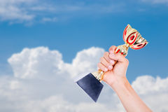 Holding winner trophy cup to blue sky. With your hand stock photos