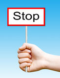 Holding a wooden sign that read: Stop Stock Image