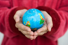 Holding world. A pair of hands holding and saving the world Royalty Free Stock Image