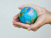 Holding world. A pair of hands holding and saving the world Royalty Free Stock Photography