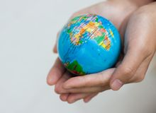 Holding world. A pair of hands holding and saving the world Royalty Free Stock Photos