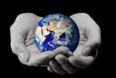 Holding the World. (2 hands holding the globe,with a soft DOF on the hands Stock Photography
