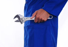Holding a Wrench by His Side. A close up of a worker holding a wrench by his side. The man is wearing a blue jumpsuit Stock Photos