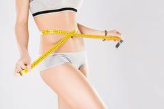 Holding yellow measuring tape on waist Stock Photo