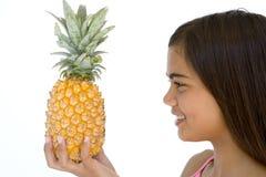 Holdingananas und -c$lächeln des jungen Mädchens Lizenzfreies Stockfoto