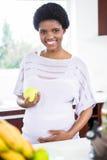 Holdingapfel der schwangeren Frau Lizenzfreie Stockfotos